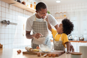 African Father and son enjoying during bake cookies at home together.