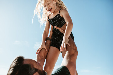 Father playing with her daughter outdoors