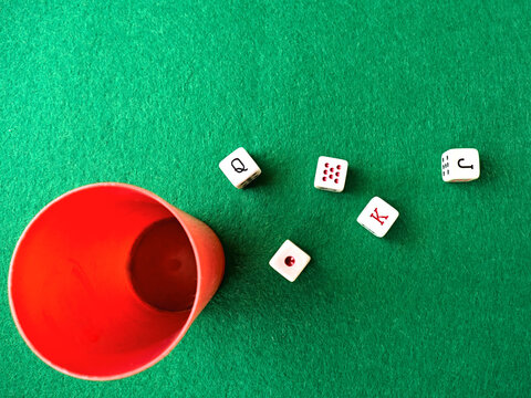 Poker dice game on a green tablecloth