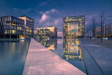Fotomurales - Illuminated City Buildings Against Sky At Dusk