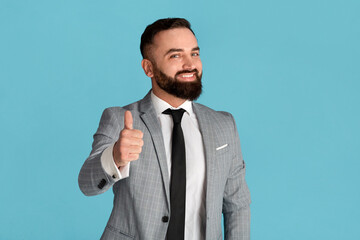 Cheerful millennial businessman showing thumb up gesture on blue background