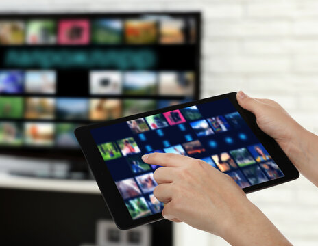 Streaming video services. Woman using tablet to change channels on TV, closeup