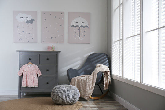 Baby room interior with cute posters and rocking chair