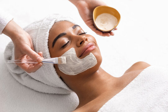 Top view of beauty therapist applying face mask