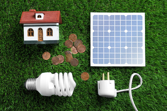Flat lay composition with solar panel, house model, light bulb and coins on green grass