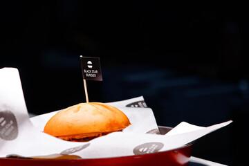 Minsk, Belarus. Oct 2019. Prepared Black Star burger for delivery to customer. Small black flag with logo of Black Star Burger restaurant inserted in top of burger. Fastfood on dark background.