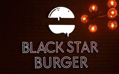Minsk, Belarus. Oct 2019. Close-up of BLACK STAR BURGER logotype on brick wall. Black star burger symbol inside the restaurant at Nemiga street. Interior element of fast food restaurant