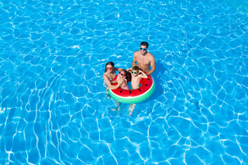 Happy family with inflatable ring in swimming pool. Summer vacation