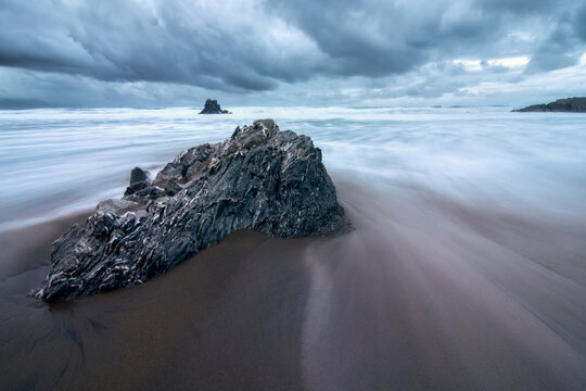 Long exposure of water flowing between a rock on the beach with stunning clouds in the background