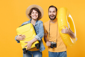 Funny young tourists couple two friends guy girl in summer clothes hat isolated on yellow...