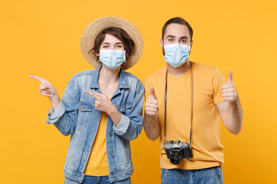Funny tourists couple friends guy girl in face mask isolated on yellow background. Epidemic pandemic coronavirus 2019-ncov sars covid-19 flu virus concept. Point index fingers aside showing thumbs up.