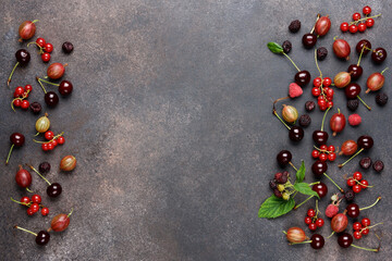 Ripe bright berries on brown background. Redcurrant, cherry, gooseberry, blackberry