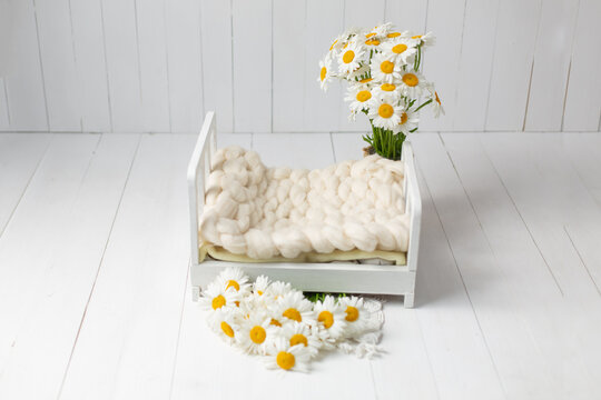 the white bed is decorated with daisies. a baby cot for a newborn photo shoot. small bed. bed for dolls