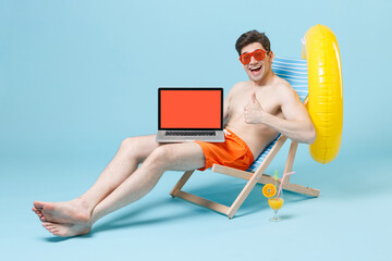 Funny young man guy in orange shorts glasses sit on deck chair isolated on blue wall background....