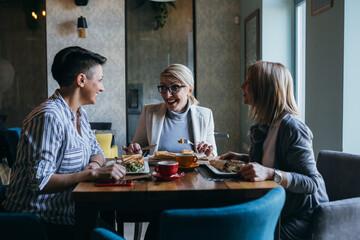 group of women friends having lunch in restaurant