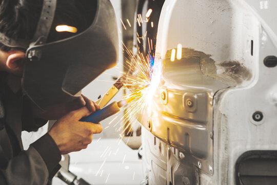Worker in mask welds car in auto service of bodywork.