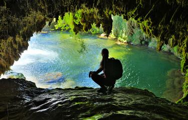Obraz beautiful cave with blue lake and woman tourist - fototapety do salonu