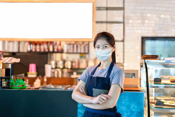 Woman in small business owner wearing medical mask at the counter in cafe.