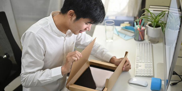A smart man is unboxing a cardboard box from shopping online at the white working desk.