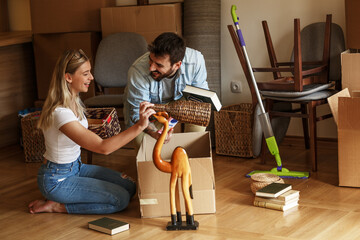 Married couple unpacking cardboard boxes at new home.Moving house concept.