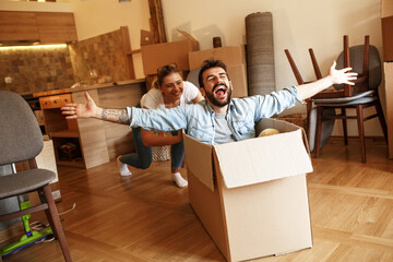 Young married couple moving into a new home.Man sitting in cardboard box while woman pushes him all over the room.Real estate funny concept