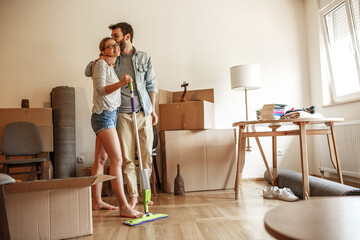 Young couple moving into new home.They standing in living room and embracing each other.