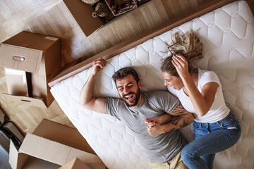 Young married couple moving into new home.They lying in bed room and relaxing after unpacking.