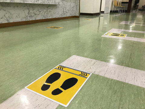 The social distancing sign stickers are on the floor of the school community to prevent the covid19 virus infection