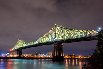 Fotomurales - Illuminated Bridge Over River Against Sky At Night