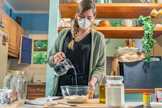 Coronavirus. Isolated pretty woman with face mask on quarantine, cooks in the kitchen at home during coronavirus crisis. Stay at home. Enjoy cooking at home. Family concept. Beautiful rustic kitchen.