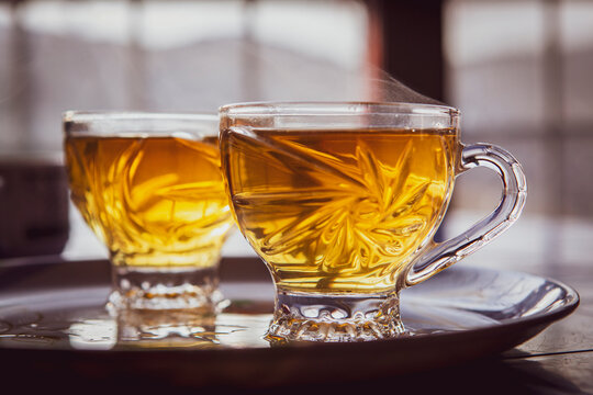 Tea cups with hot beverage with out of focus windows background. Comfort of a hot drink in a cold winter or autumn day.