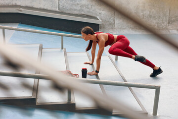 échauffer efficacement Woman Warming Up On Stairs Before Fitness Workout. Fit Girl In Fashion Sporty Outfit Exercising On Stadium. Female With Athletic Muscular Body Training Outdoor. Training In City As Urban Lifestyle.