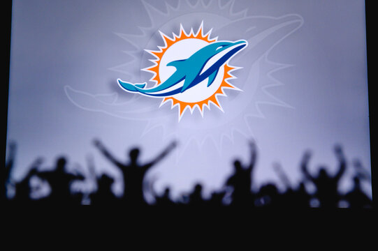 Miami Dolphins. Fans support professional team of American National Foorball League. Silhouette of supporters in foreground. Logo on the big screen.