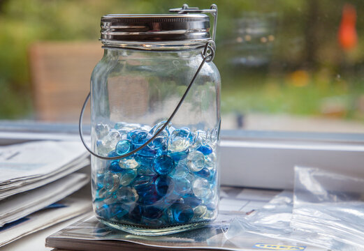 Close-up Of Marbles Glass Jar On Table