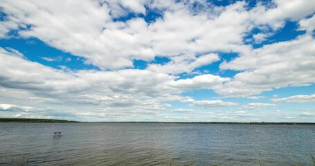Fototapete - Summer landscape with lake, blue sky and clouds. Nature wilderness 4k time lapse. Countryside outdoors, relaxation, space scenic. Beautiful pond, forest, green meadow with reflection in water.