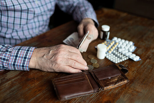 Hands of an old man counting money for medicine. Poverty, disease, low income in old age.