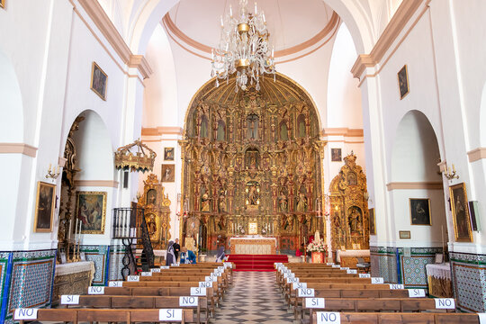 Huelva, Spain - May 8, 2020: Main Altar of St. Sebastian church in the village of Higuera de la Sierra in Huelva mountains. The benches are marked with yes/no (si / no) indications due to COVID-19