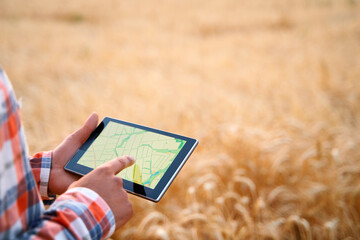 Precision farming. Farmer hands hold tablet using online data management software with maps at...
