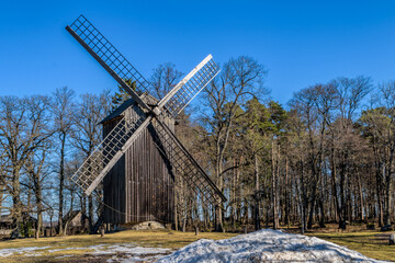 Traditional old-style wood windmill  surrounded by coniferous forest at sunny spring day. Estonia
