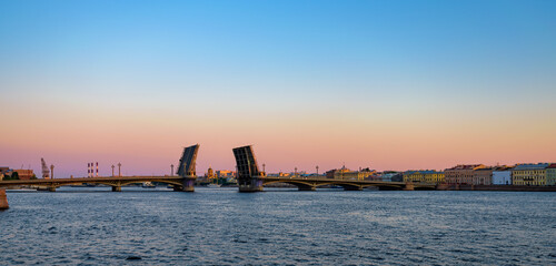 Sunrise panorama of Neva river with opened Annunciation (Blagoveshchensky) drawbridge with raised spans and Vasilyevsky island after summer white night. Saint-Petersburg, Russia.