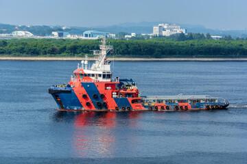 Offshore tug/Supply ship passes underway along the Singapore island shoreline in Johor strait.