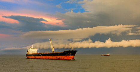 Bulk carrier vessel is awaiting loading of bauxite ore at outer anchorage of Kamsar port, Guinea, West Africa.