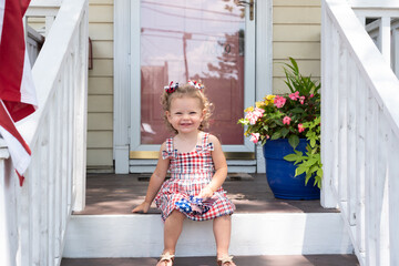 Cute toddler girl sitting on the front porch of a suburban home
