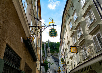 SALZBURG, AUSTRIA - JULY 25, 2017.  The Getreidegasse , famous shopping street in the Salzburg's Old City, Mozart's Birthplace ,destination for visitors from around the world. St.Blaise's church.