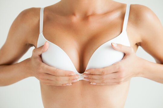 Midsection Of Woman Holding Breasts Against White Background