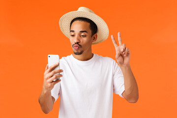 Cute and happy african-american guy in white t-shirt, summer hat, showing peace sign, taking selfie with filter fold lips kiss, looking at smartphone, post pictures from vacation, orange background