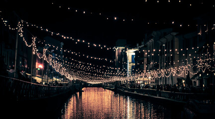 Illuminated Lights Hanging Over Canal In City At Night