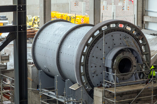Close up view of the large ball and sag mill in the mine plant. A typical type of fine grinder is the ball mill. A slightly inclined or horizontal rotating cylinder is partially filled with balls.