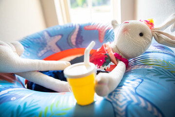 relaxing toy bunny with drink with straw on swim float