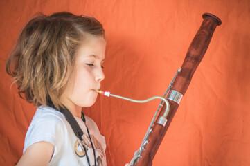 Obraz Side View Portrait Of A Girl Playing Bassoon - fototapety do salonu
